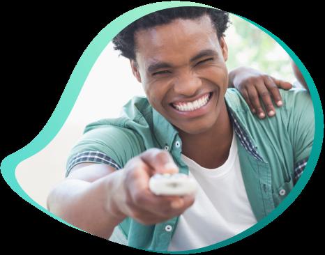 homem jovem negro sorrindo segurando controle e trocando canal de tv por assinatura