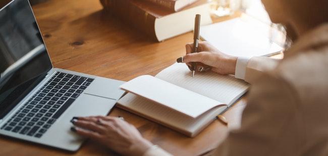 mulher escrevendo em um caderno de anotações enquanto usa um notebook