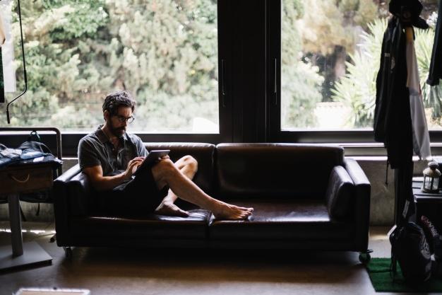 homem-sentado-em-sofa-mexendo em-tablet