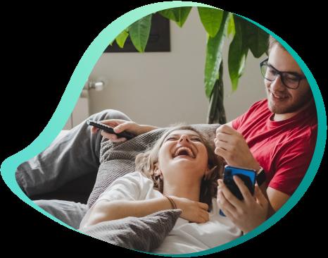 casal assisintdo tv e acessando a internet no celular com um serviço de combo