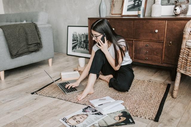 mulher-no-computador-enquanto-fala-no-telefone